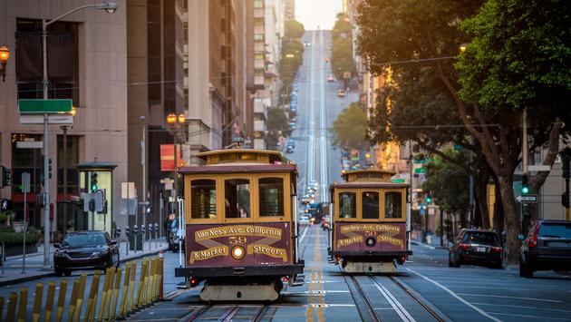 Classic view of historic traditional Cable Cars riding on famous California Street in beautiful early morning light at sunrise in summer, San Francisco, California, USA (photo via bluejayphoto / iStock / Getty Images Plus)
