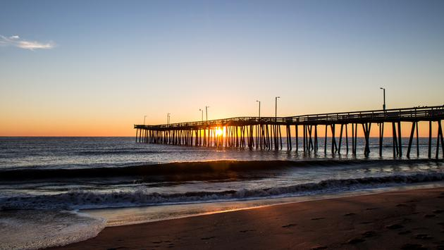 Sunrise with the Virginia Beach fishing pier in silhouette and the beach in the foreground.