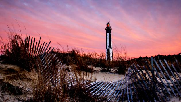 The sun goes down on the new Cape Henry Lighthouse. (photo via tmersh / iStock / Getty Images Plus)