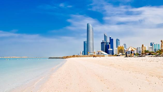 sunny beach and cityscape in Abu Dhabi, UAE (photo via vlarub/iStock/Getty Images Plus)
