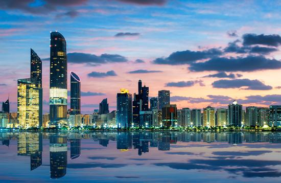 View of Abu Dhabi Skyline at sunset, United Arab Emirates (photo via vwalakte/iStock/Getty Images Plus)