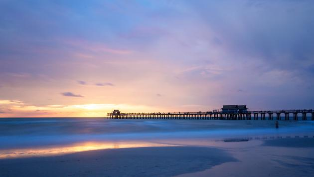 The sun goes down at the Naples Pier in the Gulf of Mexico, Southwest Florida, USA. Amazing spot of the sun coming down at blue hour in this idyllic place for family vacation and relax. (poladamonte / iStock / Getty Images Plus)