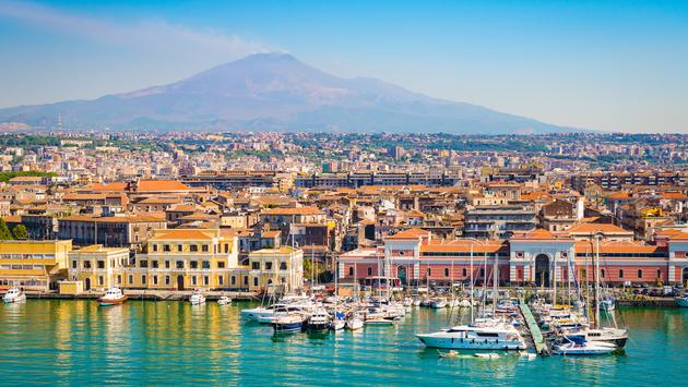 Beautiful view of Catania cruise port with smoking volcano Etna in the background. (Photo via  NAPA74 / iStock / Getty Images Plus)