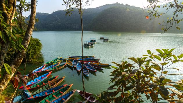 Colorful canoe boats at sunrise on Phewa Lake in Pokhara, Nepal. (Jeff_Cagle / iStock / Getty Images Plus)