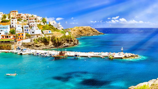 Harbour with marine vessels, boats and lighthouse. Panoramic view from a cliff on a Bay with a beach and architecture Bali (Photo via chasdesign / iStock / Getty Images Plus)