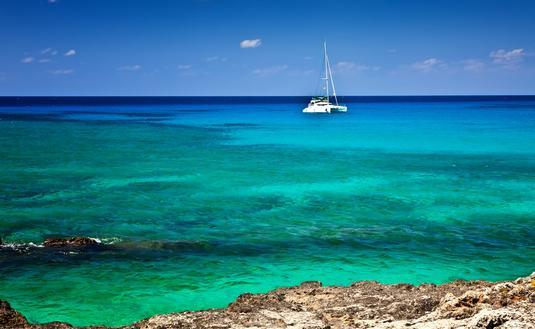 Large catamaran sailing in Grand Cayman, Cayman Islands (photo via fallbrook/iStock/Getty Images Plus)