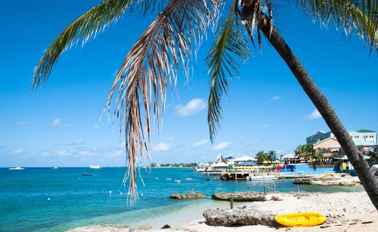 View of George Town coastline on Grand Cayman island (photo via virsuziglis/iStock/Getty Images Plus)