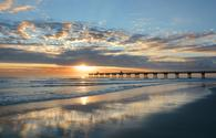 Sun rising over horizon and pier, beach illuminated with sunlight, beautiful sky reflected on the beach. Jacksonville Florida, USA. (photo via MargaretW / iStock / Getty Images Plus)