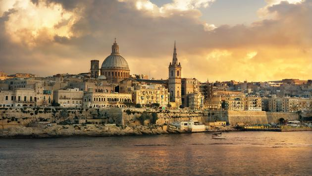 Panoramic view of Valletta at sunset with Carmelite Church dome and St. Pauls Anglican Cathedral. Malta (photo via Bareta / iStock / Getty Images Plus)