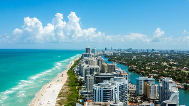 Looking down South Beach in Miami. Full view of the beach on the left and the city on the right. Beautiful blue sky on a clear day.  (photo via ULora / iStock / Getty Images Plus)