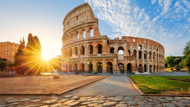 View of Colosseum in Rome and morning sun, Italy, Europe. (photo via vwalakte / iStock / Getty Images Plus)