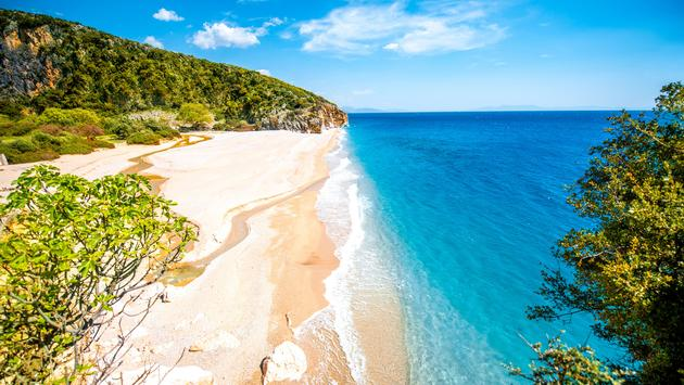Gjipe beach with rocks and river in Albania (photo via RossHelen/iStock/Getty Images Plus)