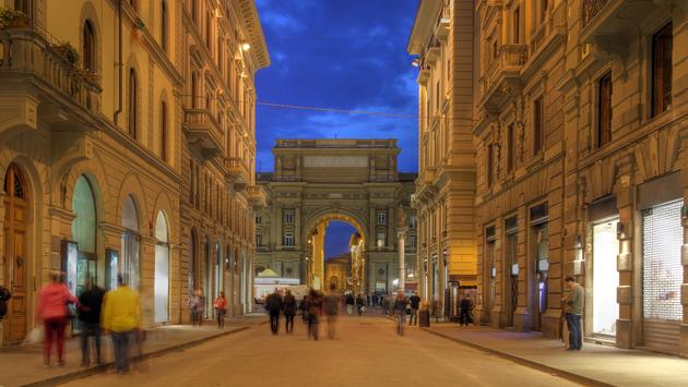 Pedestrian street at night in downtown Florence, Tuscany, Italy. The street (Via degli Speziale) is leading towards the Republic Square (Piazza della Repubblica) with the Arch (Arcone) in the background. (photo via repistu / iStock / Getty Images Plus)