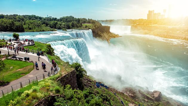 American side of Niagara falls, NY, USA. Tourists enjoying beautiful view to Niagara Falls during hot sunny summer day. (JANIFEST / iStock / Getty Images Plus)