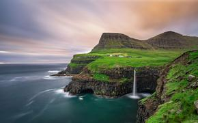 Gasadalur village and its iconic waterfall, Vagar, Faroe Islands, Denmark. Long exposure. (photo via miroslav_1 / iStock / Getty Images Plus)