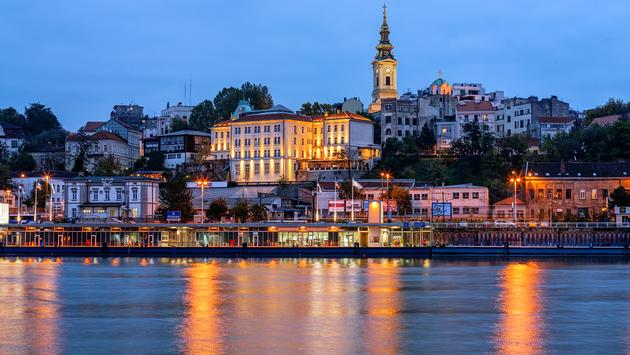 Panorama of Belgrade at night with river Sava (photo via vladimir_n / iStock / Getty Images Plus)