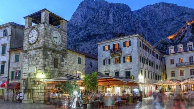 Scene in the medieval town of Kotor, Montenegro at twilight, featuring the Square of Arm and the clock tower near the Maritime entrance gate. (repistu / iStock / Getty Images Plus)