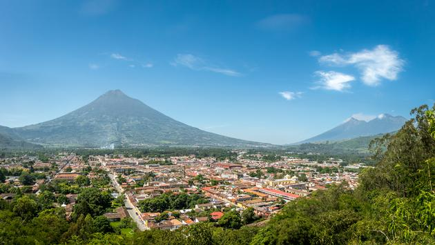 View of Antigua Guatemala with the three volcanoes.  (photo via: diegograndi/iStock/Getty Images Plus)