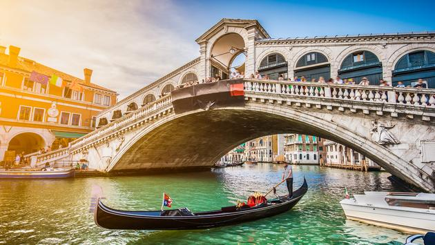 Beautiful view of traditional Gondola on famous Canal Grande with Rialto Bridge at sunset in Venice, Italy with retro vintage Instagram style filter and lens flare effect. (photo via bluejayphoto / iStock / Getty Images Plus)