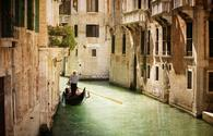 Gondola travels down the canals of Venice in Italy (photo via BrianAJackson / iStock / Getty Images Plus)