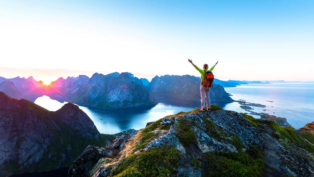 Happy woman hiker enjoying scenic view of midnight sun at the top of Reinebringen hike above Reine village in the Lofoten archipelago during arctic summer, Norway (NicoElNino / iStock / Getty Images Plus)