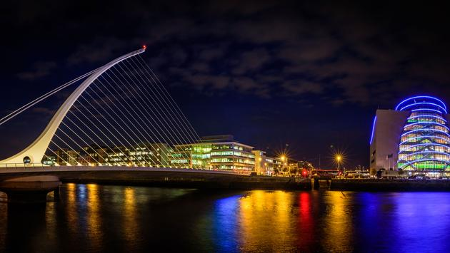Panorama of Dublin by night. River with citylights reflections. Samuel Beckett Bridge. (photo via muzzyco / iStock / Getty Images Plus)