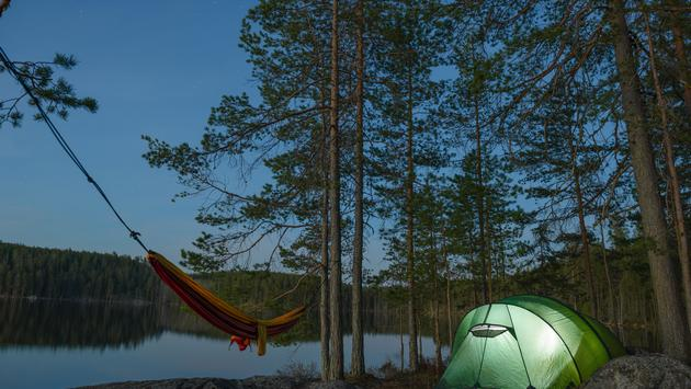 Tent camp for two backpackers in Repovesi National Park in Finland. (photo via tahkani / iStock / Getty Images Plus)