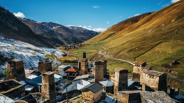 Svan Towers in Ushguli and Inguri river in autumn. One of the highest inhabited village in Europe. Caucasus, Upper Svaneti, Georgia (photo via bortnikau/iStock/Getty Images Plus)