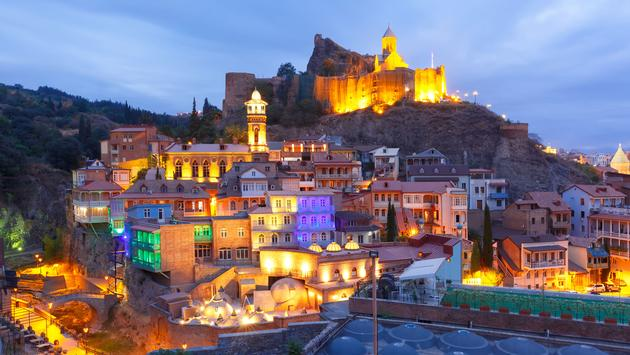 View of Narikala ancient fortress with St Nicholas Church, Jumah Mosque in old historic district Abanotubani in night Illumination during morning blue hour, Tbilisi, Georgia (photo via KavalenkavaVolha/iStock/Getty Images Plus)