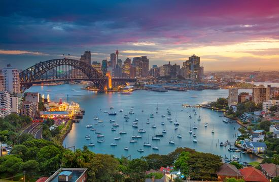 Cityscape image of Sydney, Australia with Harbour Bridge and Sydney skyline during sunset. (photo via RudyBalasko / iStock / Getty Images Plus)