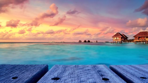 Beautiful sunset over the sea on a cloudy day in Maldives. (photo via Salawin / iStock / Getty Images Plus)